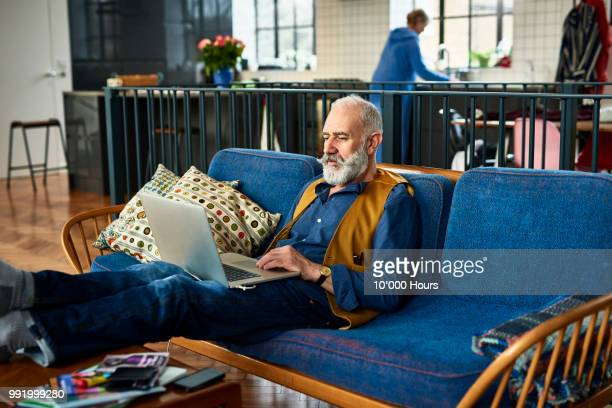 Senior man with trendy moustache working on laptop at home