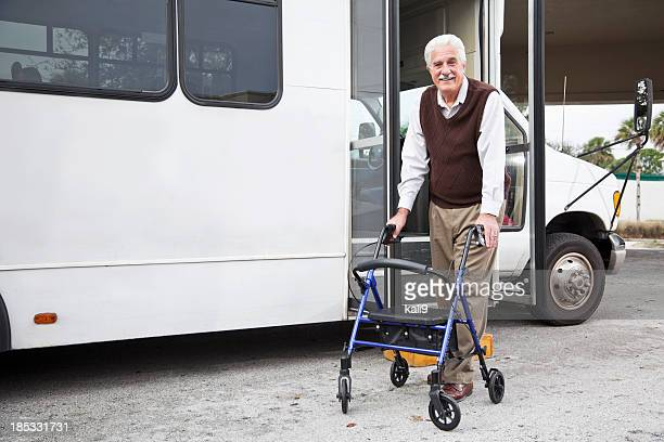 senior man with walker exiting shuttle bus - transportation stock pictures, royalty-free photos & images