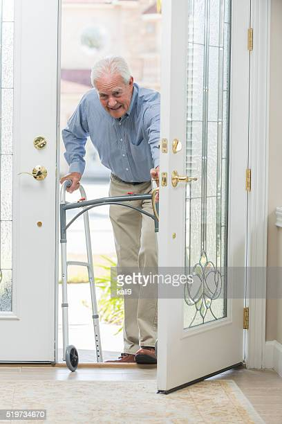 Senior man with walking coming home thru front door