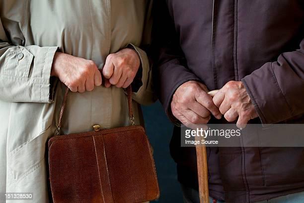 Senior man with walking stick, senior woman with handbag