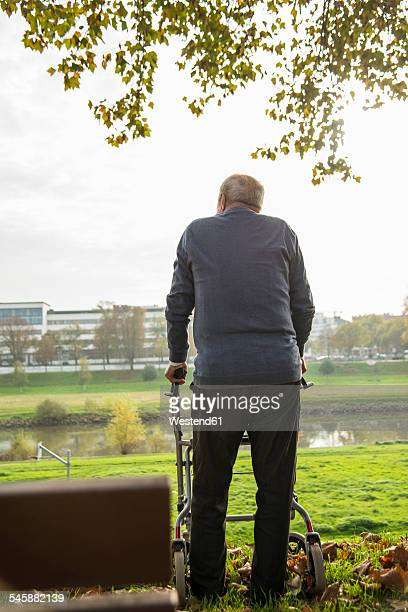 Senior man with wheeled walker by the riverside
