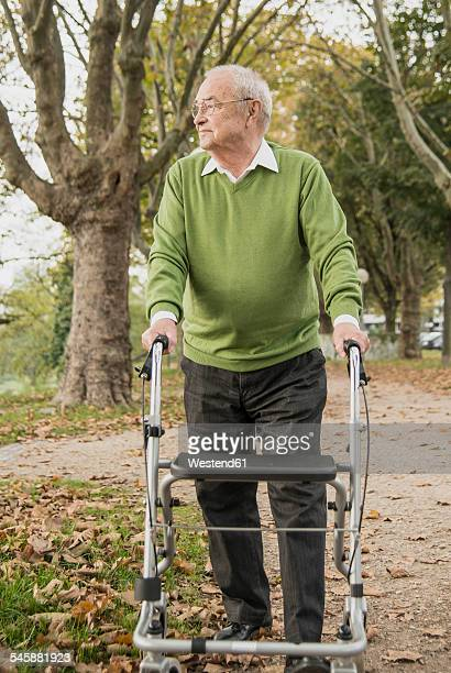 Senior man with wheeled walker in park