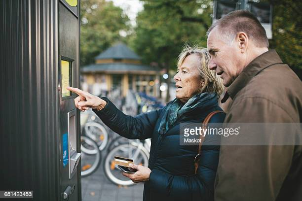senior man with woman making payment through credit card at bike rental station - bicycle parking station stock photos and pictures