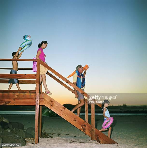 Senior man, woman, girl and boy (6-8) descending steps to beach
