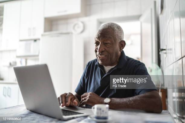 senior man working at laptop at home - senior adult stock pictures, royalty-free photos & images