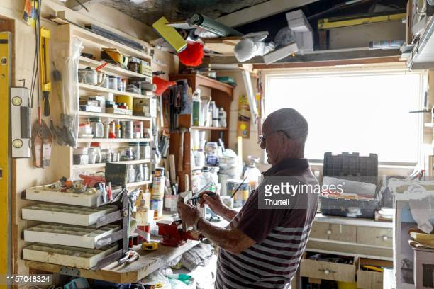 senior man working in his workshop - man cave stock pictures, royalty-free photos & images