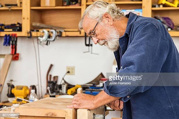 Alter Mann arbeitet im der Werkstatt