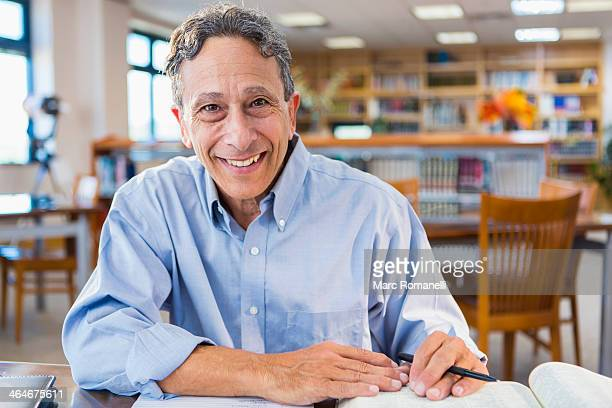 senior man working in library - college professor stock photos and pictures