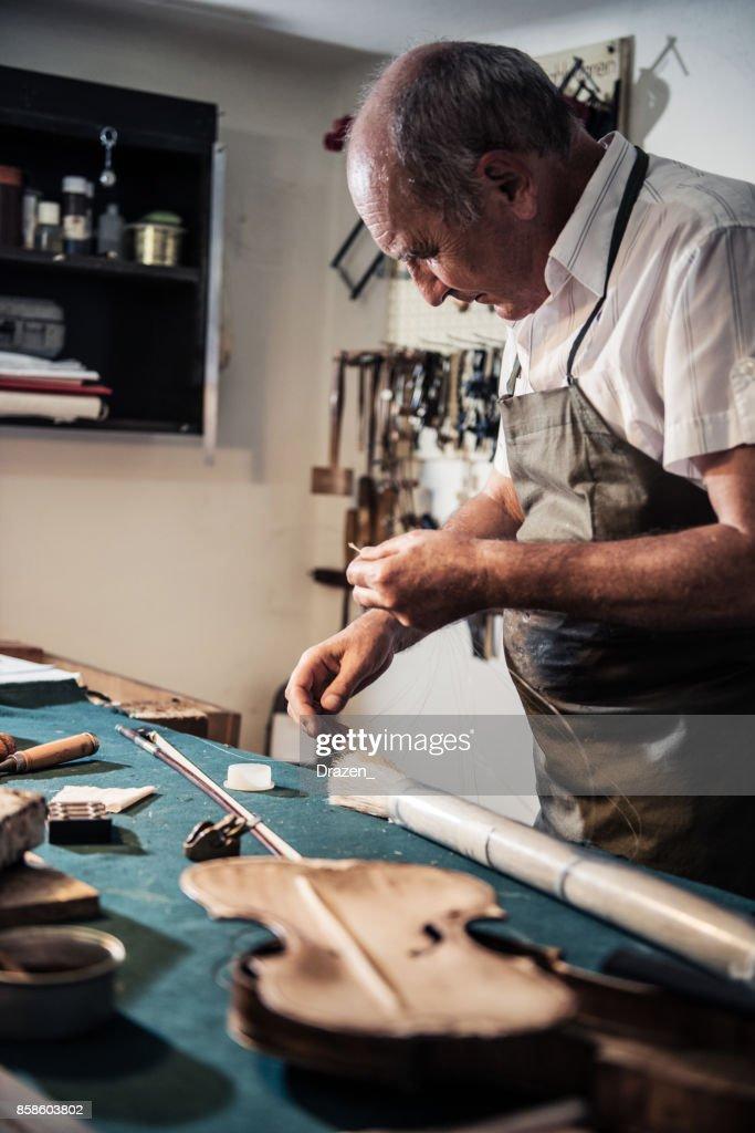 Ältere Mann arbeitet in Musik-Instrument-Shop und Reparatur Bogen : Stock-Foto