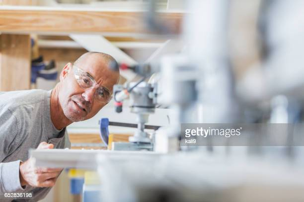 Senior man working in shutter factory on machinery