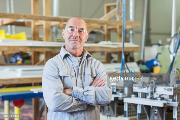 senior man working in shutter factory - working seniors stock pictures, royalty-free photos & images