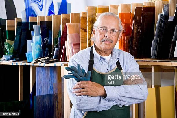 Homme Senior travaillant en studio en verre teinté atelier
