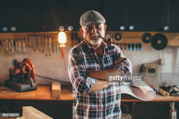 senior man working in workshop - pipe smoking pipe stock photos and pictures