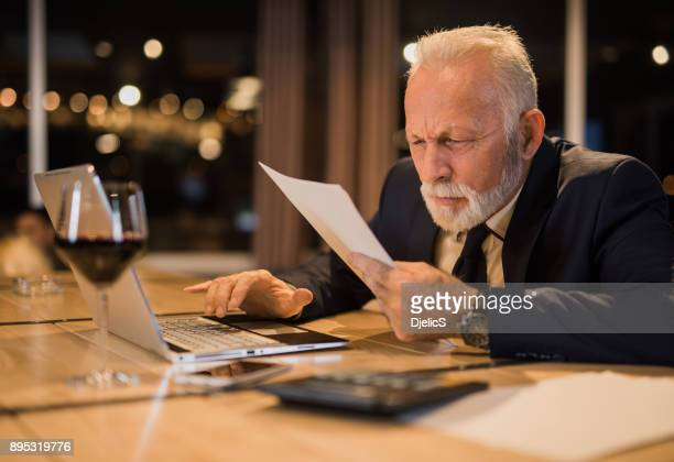 senior man working late and struggling to read a document. - effort stock pictures, royalty-free photos & images