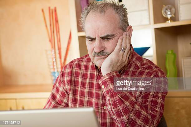 Senior man working on a laptop at home