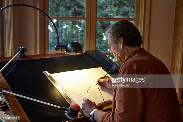 Senior man working on architectural drawing at home