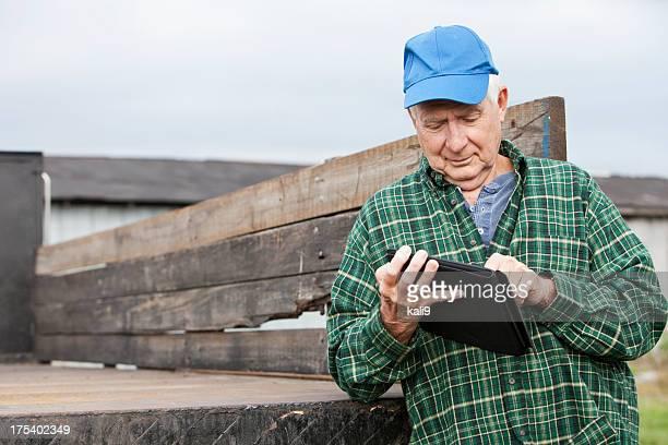 Homme Senior travaillant avec une tablette numérique de la ferme