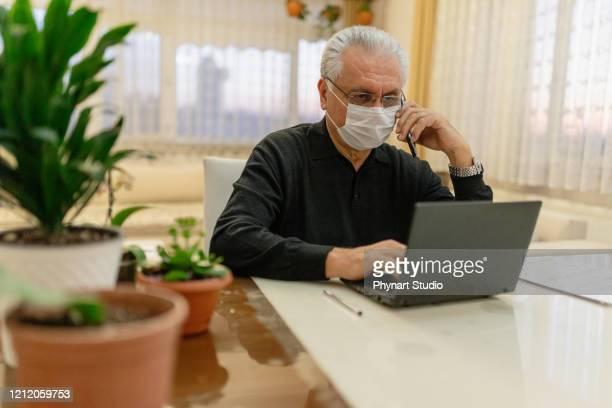homem sênior trabalhando em laptop em casa - business finance and industry - fotografias e filmes do acervo