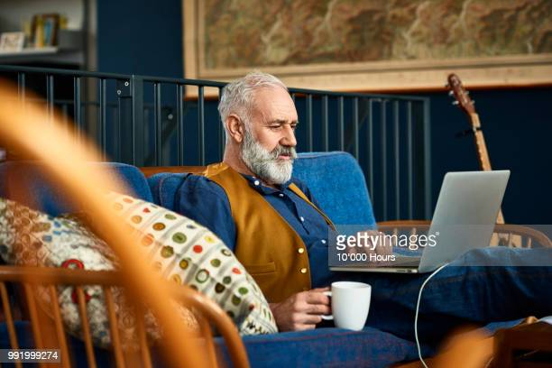 senior man working on laptop at home with serious expression - mood stream stock pictures, royalty-free photos & images