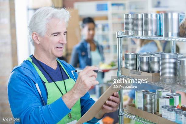 Senior man works on inventory in community food bank