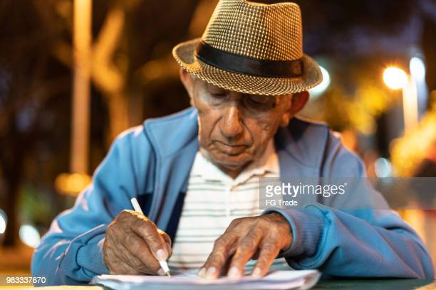 senior man writing - form filling stock pictures, royalty-free photos & images