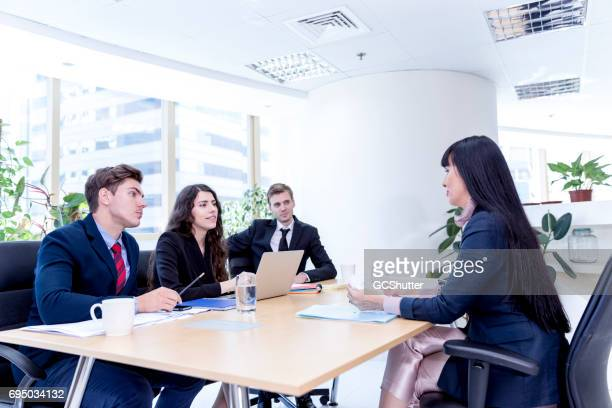 Senior management team taking the interview of a businesswoman
