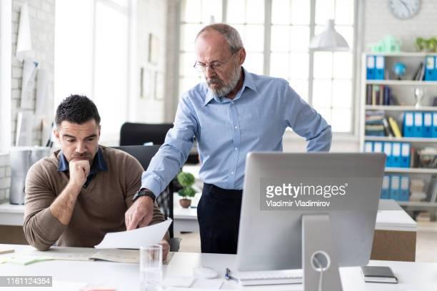 gerente sênior que explica ao colega de trabalho algo no computador - brigar - fotografias e filmes do acervo