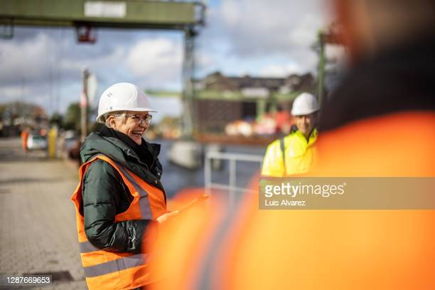 senior manager having meeting with team at large commercial dock - harbour stock pictures, royalty-free photos & images
