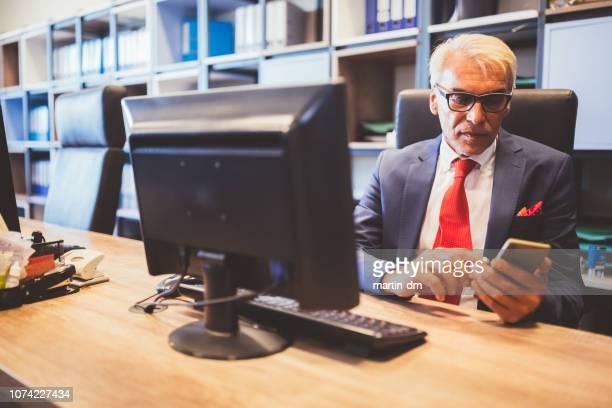 スマート フォンでオフィス テキスト メッセージでシニア マネージャー - 酋長 ストックフォトと画像