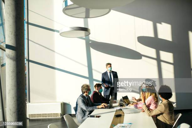 senior manager leading the meeting - employment issues stock pictures, royalty-free photos & images