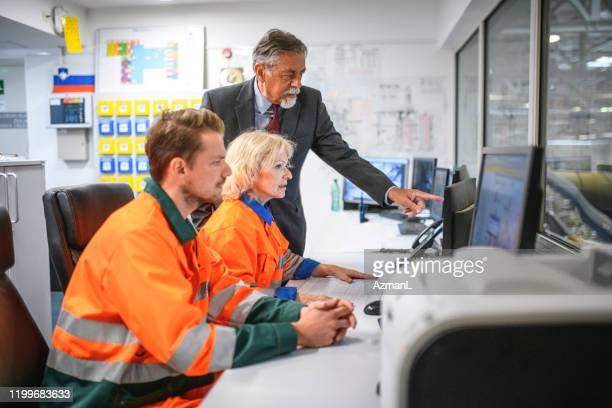 senior manager observing workers in recycling control room - waste management stock pictures, royalty-free photos & images