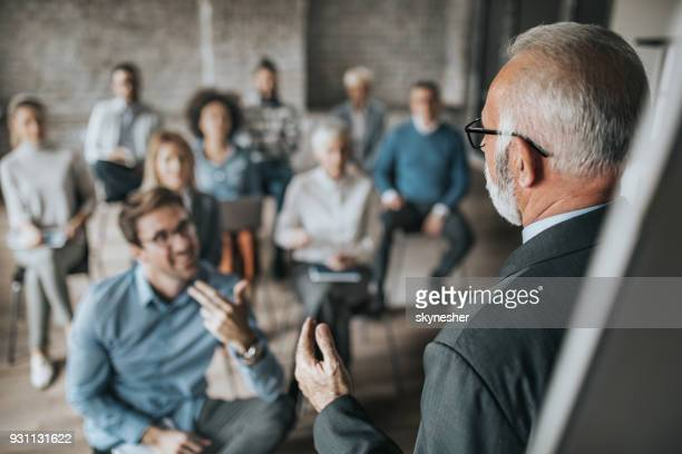 Senior manager talking to large group of his colleagues on a business seminar.