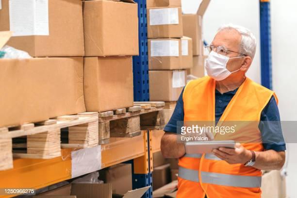 保護フェイスマスクを着用し、デジタルタブレットを使用し、倉庫で働くシニアマネージャー - ワーキングシニア ストックフォトと画像