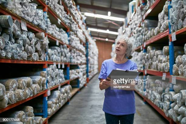 senior manager with clipboard looking at carpets - working seniors stock pictures, royalty-free photos & images