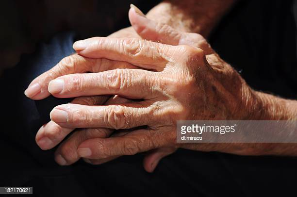 senior man's arthritic hands in shadow. - arthritis stock pictures, royalty-free photos & images