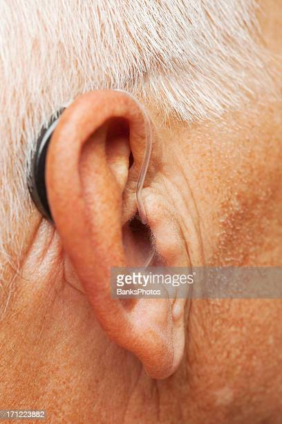 senior man's ear with hearing aid - earlobe stock photos and pictures