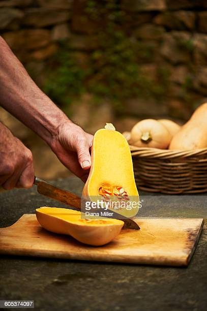 Senior mans hands chopping butternut squash with knife on cutting board