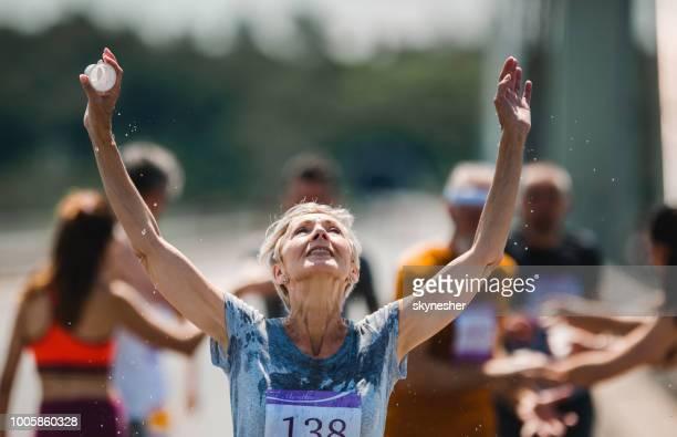 シニアのマラソン ランナーは、レース中に水と自分自身を更新します。 - ハーフマラソン ストックフォトと画像