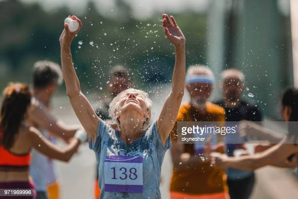 senior marathon runner refreshing herself with water during a race. - maratona foto e immagini stock