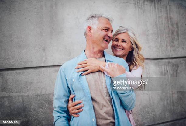 Senior married couple hugging and laughing together on city break