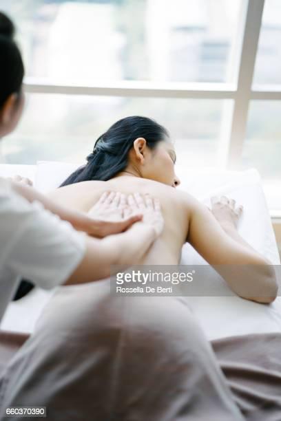 senior massage therapeut maken olie massage met een jonge vrouw - thai massage stockfoto's en -beelden