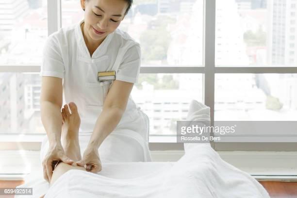 Senior masseuse making foot massage