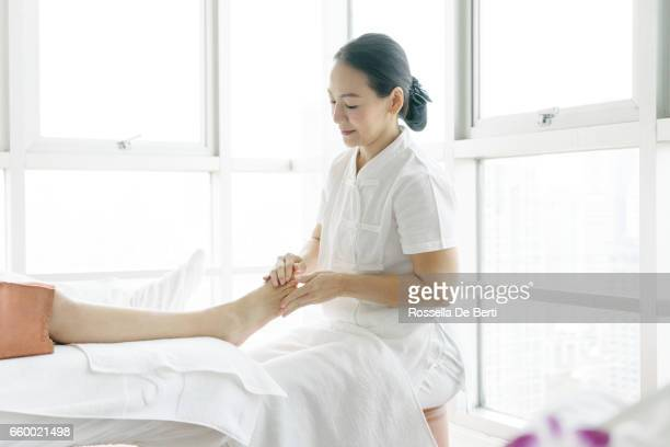 senior masseuse making foot massage - foot massage stock pictures, royalty-free photos & images