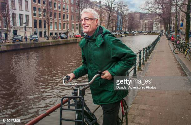 senior mature handsome gray hair older man with his bicycle in amsterdam on a chilly day - amsterdam stock pictures, royalty-free photos & images