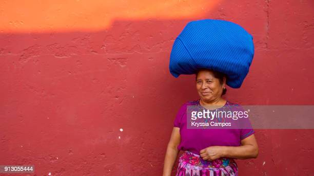 senior mayan woman in typical costume with bundles balanced on her head. antigua - guatemala. - mayan people stock photos and pictures