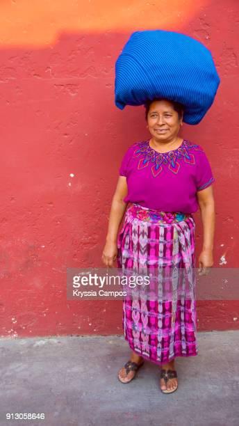 Senior mayan woman in typical costume with bundles balanced on her head. Antigua - Guatemala.