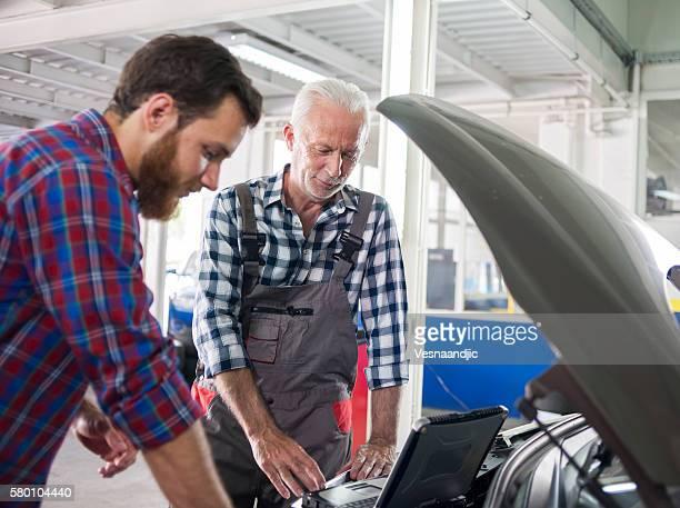 Senior mechanic at work in his garage with customer