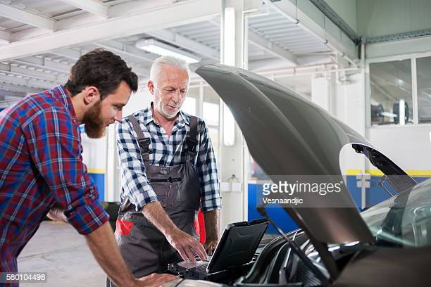 Senior mechanic at work in his garage with customer