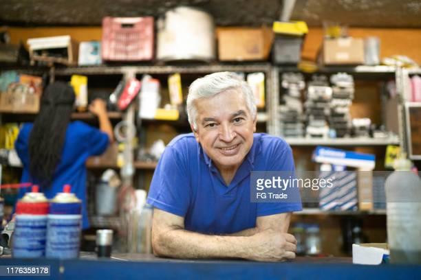 mecânico sênior que behing um contador que trabalha em uma auto loja de reparo - pequeno - fotografias e filmes do acervo