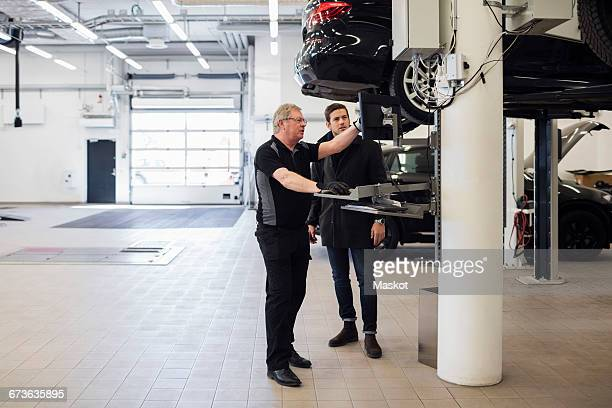 Senior mechanic explaining customer while standing at repair shop
